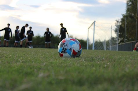 Photo taken by Blake Taylor. Players warming up in the background of a soccer ball on the CCHS practice field